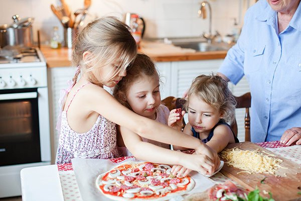 Kids are cooking italian pizza together with nanny