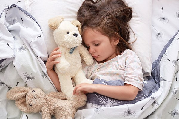 Close up portrait of cute little girl sleeping peacefully and hugging her stuffed toys in bed