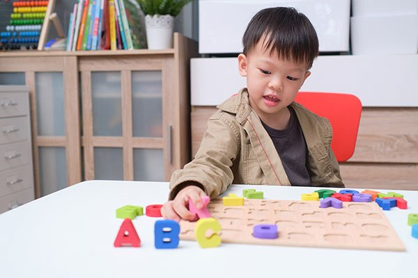 young boy playing with alphabet blocks